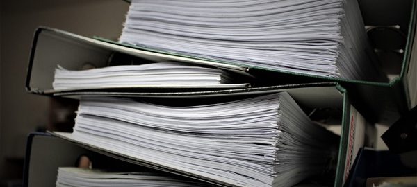 pile of binders with paper work. learn about 3. Business Continuity, Disaster Planning, Business Interruption with HardeRisk