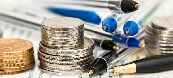 stacks of coins and pens on insurance form. learn about self-insurance with robert harder consulting inc.